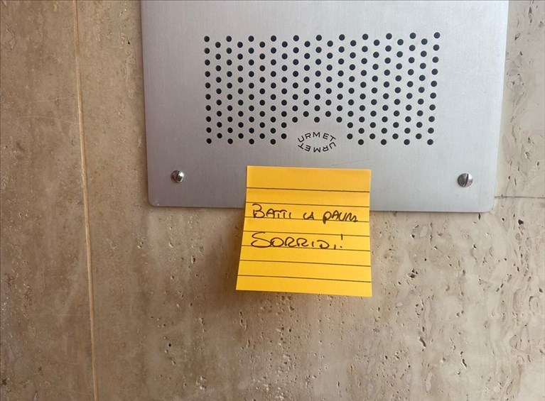 La città invasa di post-it colorati con la frase Batti la paura, sorridi!